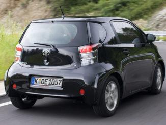 Kurvenfahrt eines schwarzen Toyota iQ auf einer Landstraße.