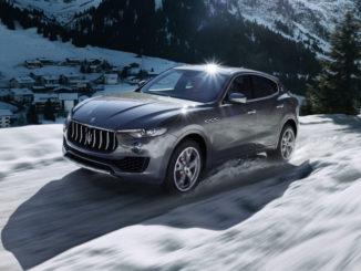 Ein grauer Maserati Levante S fährt auf einem Gebirgspass durch den Schnee.