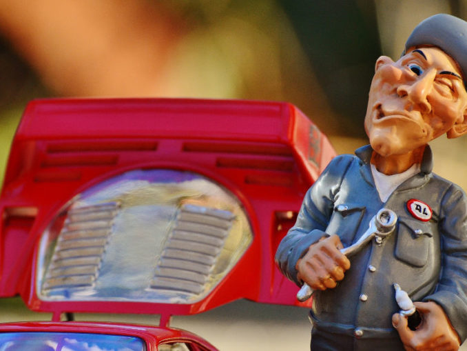 Spielzeugfigur eines mürrisch dreinblickenden Automechanikers neben einem Spielzeugauto.