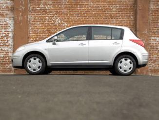 Ein silberner Nissan Versa steht in den USA vor einer Ziegelmauer, in Europa heißt das Modell Tiida