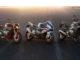 Die drei Motorräder BMW S 1000 R, RR und XR stehen bei Sonnenuntergang auf einer großen Teerfläche.