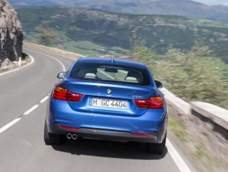 Ein blaues BMW 428i Gran Coupé fährt auf einer Bergstraße auf eine Kurve zu.