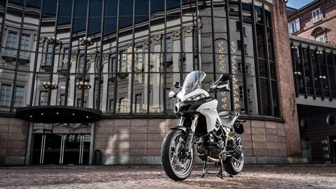 Eine weiße Ducati Multistrada 950 steht vor einem Geschäftshaus.