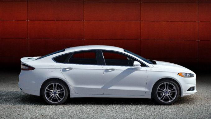 Ein weißer Ford Fusion (Mondeo) Titanium des Modelljahres 2014 steht vor einer roten Wand.
