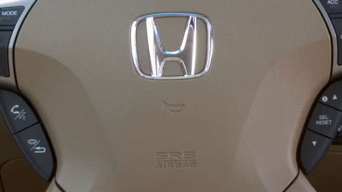 Beiges Lenkrad eine Honda Legend von 2006 mit Logo und Symbol des Airbags und der Hupe.