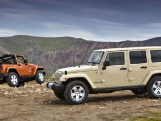 Zwei Jeep Wrangler, ein roter Zweitürer und ein beiger Viertürer, stehen im Gelände vor einer Bergkulisse.