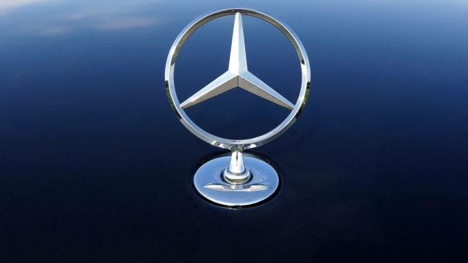 Ein Mercedes-Stern in Großaufnahme auf einer blauen Motorhaube.