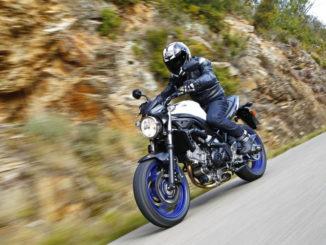 Eine schwarze Suzuki SV650 mit blauen Rädern fährt auf einer Landstraße.