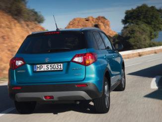 Blick auf das Heck eines blauen Suzuki Vitara bei der Anfahrt auf eine Kurve einer Landstraße