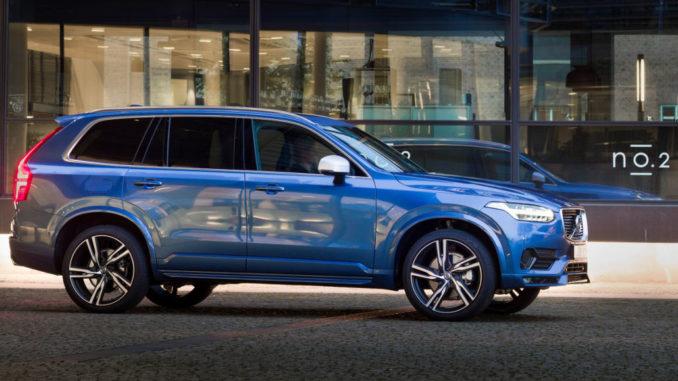 Ein blauer Volvo XC90 des Modelljahres 2017 fährt an einem Bürogebäude vorbei.