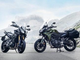 Zwei Yamaha Tracer 900 des Modelljahrs 2017 stehen auf einem Pass vor einer Bergkulisse.