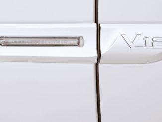 Das silberne V12-Logo an der Seite eines weißen BMW 760Li
