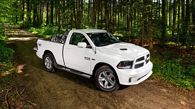 Ein weißer RAM 1500 steht auf einem Waldweg.