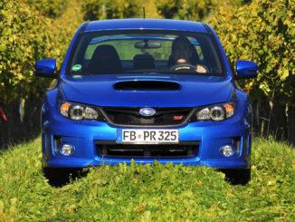 Ein blauer Subaru WRX STI fährt auf einem Grasweg in einem Weinberg