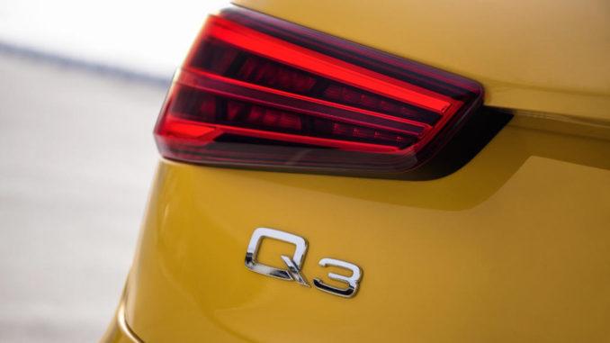 Logo der Q3-Baureihe am Heck eines gelben Audi.