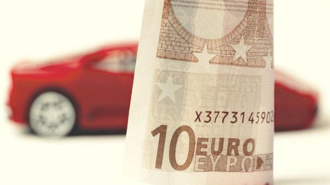 Zehn-Euro-Schein im Vordergrund und Modell eines Sportwagens im Hintergrund