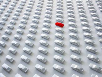 Eine Reihe weißer Autos aus Pappe, nur eines ist rot
