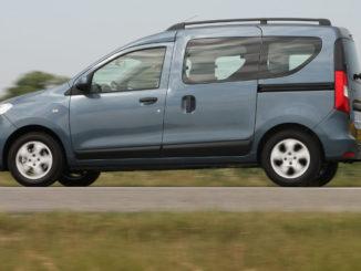 Ein blau-grauer Dacia Dokker fährt auf einer Landstraße vor einem sommerlichen Rapsfeld.