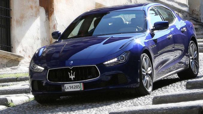 Ein blauer Maserati Ghibli fährt eine steile Straße hinab.