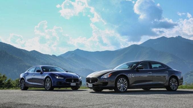 Ein blauer Maserati Ghibli und ein grauer Maserati Quattroporte, Modelljahr 2015, stehen vor einer Bergkulisse.