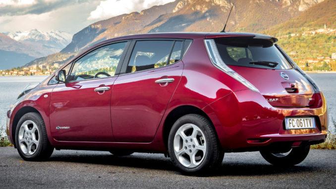 Ein roter Nissan Leaf steht vor einem See in Italien.