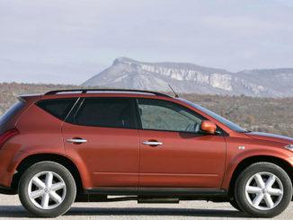 Ein kupferfarbender Nissan Murano steht vor einer Bergsilhouette.