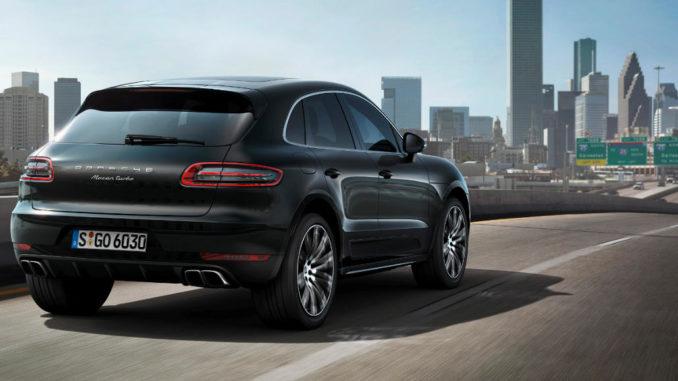 Ein schwarzer Porsche Macan Turbo fährt auf einem US-Highway auf die Skyline einer Stadt zu.