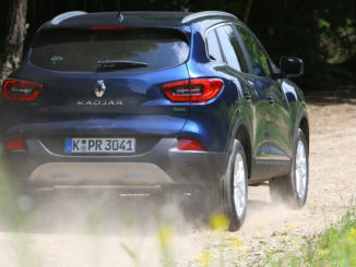 Ein blauer Renault Kadjar fährt auf einem Waldweg.