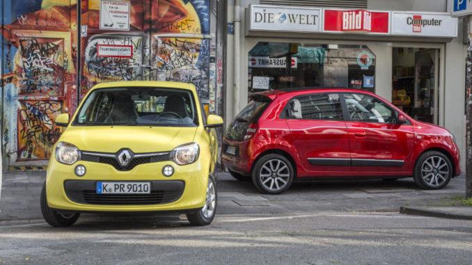 Ein gelber und ein roter Renault Twingo der dritten Generation stehen auf der Straße einer Großstadt.