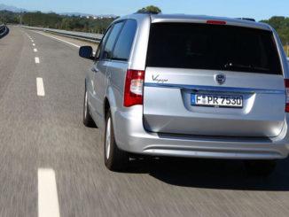 Das Heck eines silbernen Lancia Voyager fährt 2011 auf einer Landstraße.