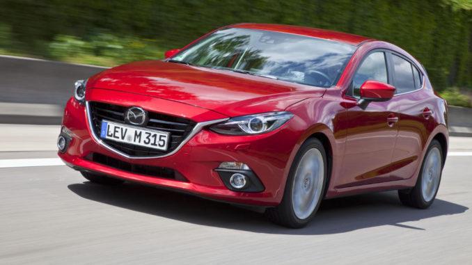 Ein roter Mazda3, fotografiert von schräg vorne, fährt auf einer Landstraße.
