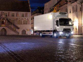 Renault Trucks D Wide mit Assistenzsystemen Spurhaltekontrolle und Notbremsassistent auf dem nächtlichen La Réunion Platz in Mühlhausen (Mulhouse)