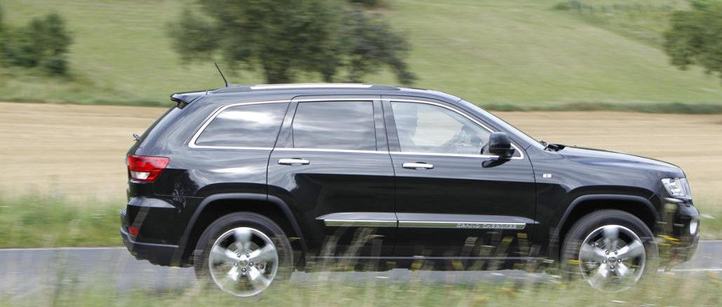 Ein schwarzer Jeep Grand Cherokee Overland Summit fährt auf der Landstraße.