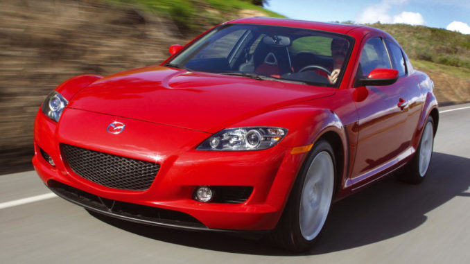 Ein roter Mazda RX-8 der ersten Generation fährtauf einer Landstraße