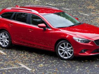 Ein roter Mazda6 (GJ), Baujahr 2012, steht auf einem Parkplatz mit Herbstlaub.