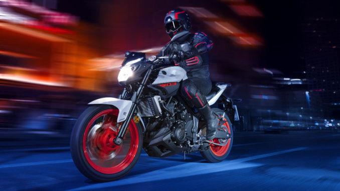 Eine grau-schwarze Yamaha MT-03 mit roten Felgen fährt durch die Nacht.