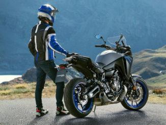 Ein Motorradfahrer steht 2020 mit einer blau-grauen Yamaha Tracer 700 an der Kurve eine Bergpasses.