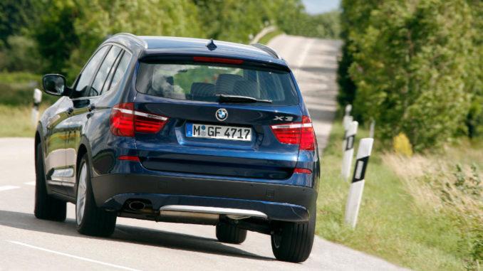 Kurvenfahrt eines blauen BMW X3 (08/2011)