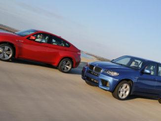 Ein roter BMW X6 M und ein blauer X5 M fahren 2009 auf einer Strandpromenade.