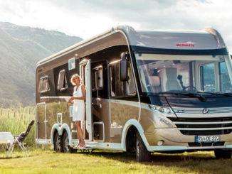 Ein beiges Dethleffs-Wohnmobil vom Typ Globetrotter XLI (MJ 2019) steht neben einem Campingtisch in einem Naturpark.