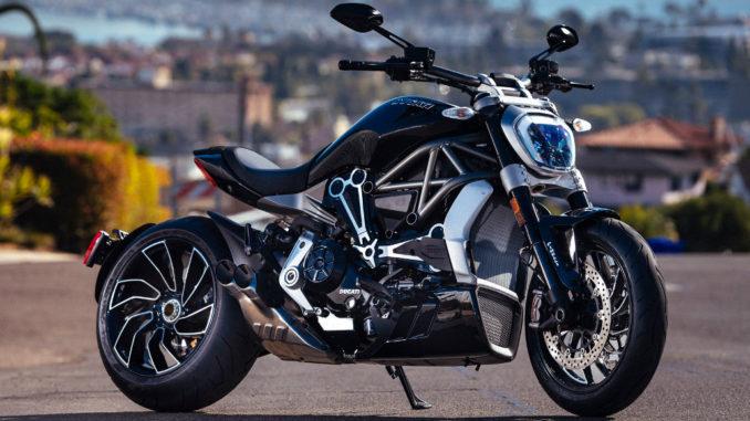 Eine schwarze Ducati XDiavel steht 2017 vor der Skyline einer Küstenstadt.