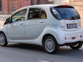 Ein weißer Mitsubishi Electric Vehicle (I-Miev) fährt an Backsteingebäuden vorbei.