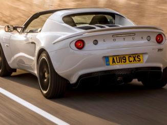 Eine graue Lotus Elise Sport 220 fährt an einer Betonwand vorbei.