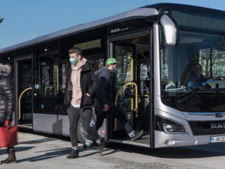 Ein silberner Omnibus vom Typ MAN Lion's City steht an einer Haltestelle in München.