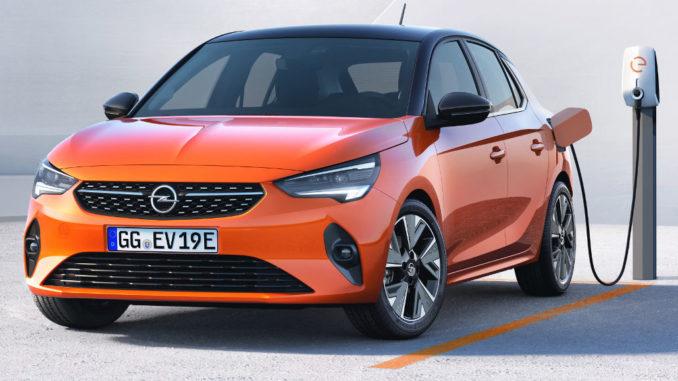 Ein orangener Opel Corsa-e steht 2020 an einer Ladesäule.