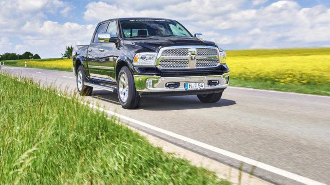 Ein schwarzer Pick-up RAM 1500 mit Autogasanlage fährt auf einer Landstraße vor einem Rapsfeld.