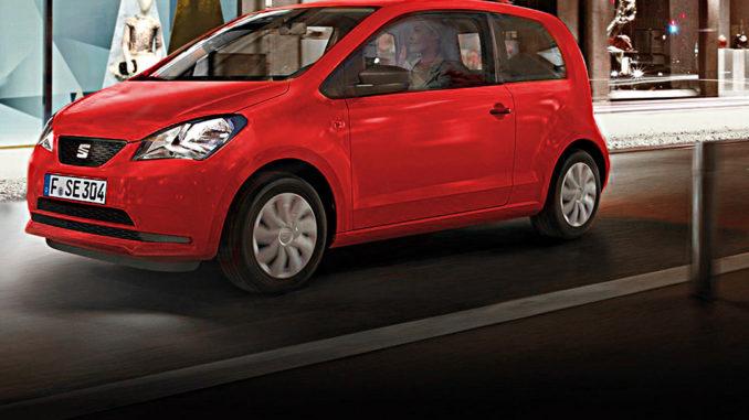 Ein roter Seat Mii fährt nachts in einer Großstadt an Schaufenstern vorbei.