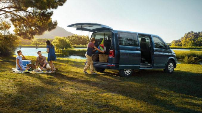 Ein blauer VW T6 Multivan steht am Rande eines Sees bei einem Familienpicknick.