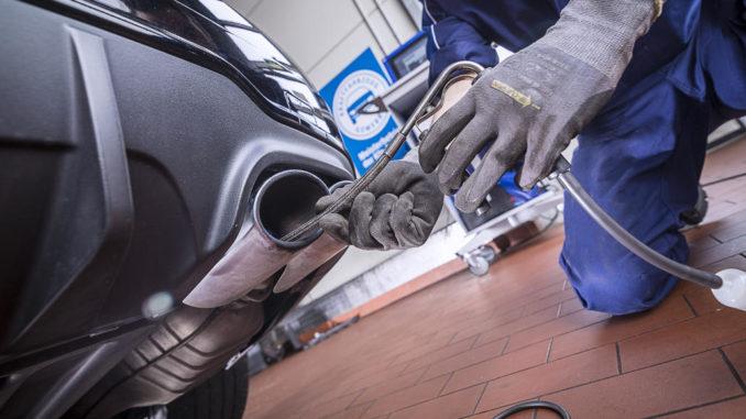 Ein Werkstattmitarbeiter führt im Rahmen einer Abgasuntersuchung eine Endrohrmessung durch.