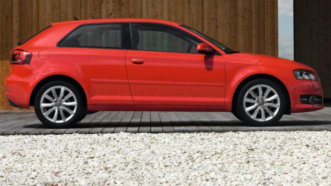Ein roter Audi A3 steht 2010 vor einer Holzfassade.